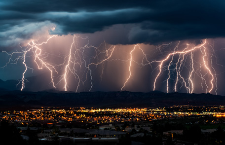 Severe lightning over a city at night